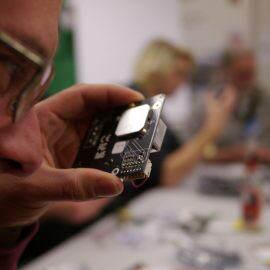 Ein Mann bastelt einen Feinstaubsensor und überprüft durch seine Brille die Steckverbindungen