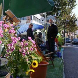 Ein umgestalteter Parkplatz ist grün und bunt, mit Blumen und anderen Pflanzen. Die Menschen fühlen sich wohl. Sonst steht hier nur Blech.
