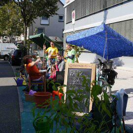 Eine muntere Gruppe von Menschen hat Park-Plätze verschönert mit Pflanzen, Stühlen, Rädern und feiert
