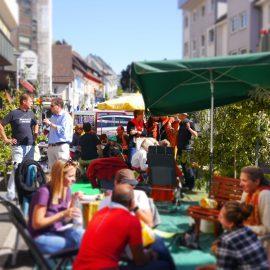 Beim PARKing Day sitzen Gäste und Passanten mit den Organisatoren zusammen, trinken Kaffee und überlegen, wie die Stadt für alle BürgerInnen noch schöner gestaltet werden kann