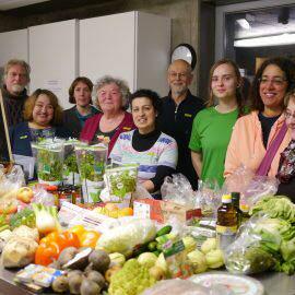 Einige Köche und Köchinnen stehen stolz hinter einem Tisch mit den geretteten Lebensmitteln für die Schnippeldisco - in Hintergrund ein Schild: Heute Schnippeldisco