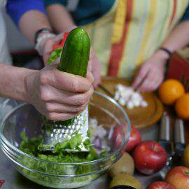 Zubereitung eines Salats mit Gurke, im Hintergrund Äpfel und Orangen