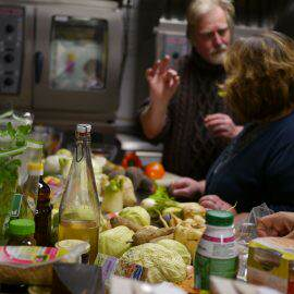 viele gerettete Lebensmittel wie Salate und Gemüse warten darauf, zu leckeren Speisen verarbeitet zu werden - im Hintergrund zwei Köche