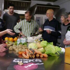 Auf einem Tisch liegen die geretteten Lebensmittel. Es wird überlegt, was sich darauf leckeres kochen lässt
