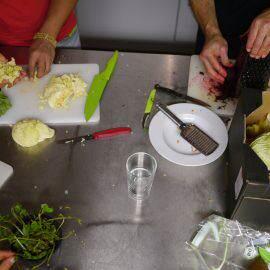 Bild von oben auf den Küchentisch bei der Schnippeldisco: Kräuter werden gehackt, Salat geschnippelt und Rotebeete geraspelt