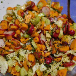 Nahaufnahme eines bunten Salats mit Möhren, Gurken, Radieschen und Blattsalat, garniert mit Kräutern