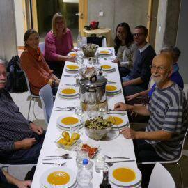 Nach dem Kochen kommt das Essen: Die fleißigen Köche und Köchinnen der Schnippeldisco sitzen am gedeckten Tisch und freuen sich auf das leckere Essen