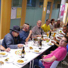An einer langen Tafel sitzen Aktive der Schnippeldisco und genießen eine Suppe
