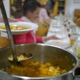 Die Teilnehmer der Schnippeldisco sitzen am gedeckten Tisch und schöpfen leckere Gemüsesuppe