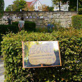 Das Ess-Gärtle - ein Schild mit Namen im Vordergrund, dahinter fleißige Gärtner