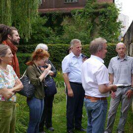 Umweltminister Franz Untersteller schaut sich interessiert einige Bilder an, die die Aktionen der Initiative Essbare Stadt Böblingen dokumentieren. Einige Aktive sowie Journalisten schauen zu