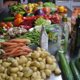 Bei der veganen Schnippeldisco verwenden wir gerettete Lebensmitel, die hier auf dem Küchentisch ausgestellt sind: Kartoffeln, Gutke, Salat, Bohnen, Pilze, Paprika, Aubergine, Kürbis, Orangen und Zwiebeln
